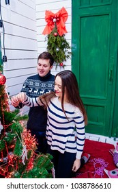 Men and women holding christmas decor in their hands