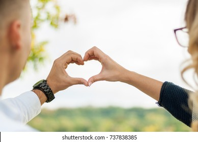 Men and women in love, make shape hearts by hand