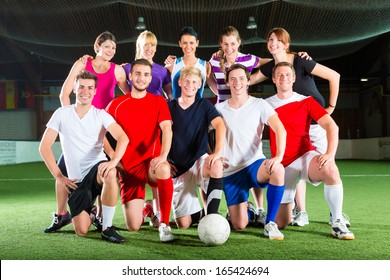 Men and women in mixed sport team playing football or soccer indoor