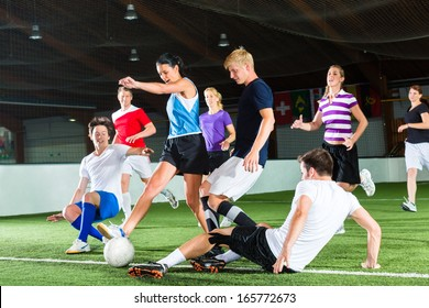 Men and women in mixed sport team playing football or soccer indoor and trying to score goal