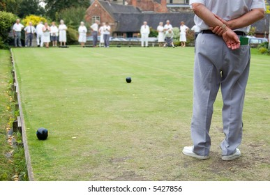 Men and women playing Flat Lawn Bowls. Focus on the man in the foreground