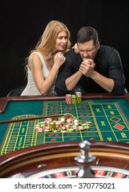 Men with women playing roulette at the casino.