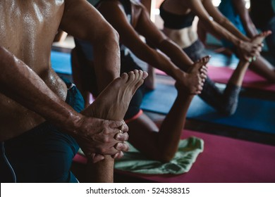 Men and women practicing yoga and meditation during yoga retreat vacation in studio