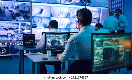 Men and women sitting at desks and browsing surveillance videos on computers near speaking mature leaders in security center