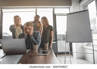 Men and women staring at laptop monitor in meeting room. Their expressions are frustrated. Copy space in right side