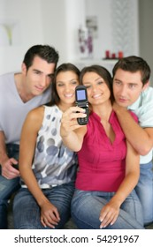 Men and women taking a picture with a mobile phone