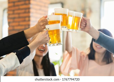 Men and women toasting with beer