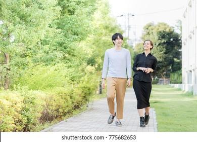 Men and women walking on a refreshing sidewalk with fresh green (internationalization image)