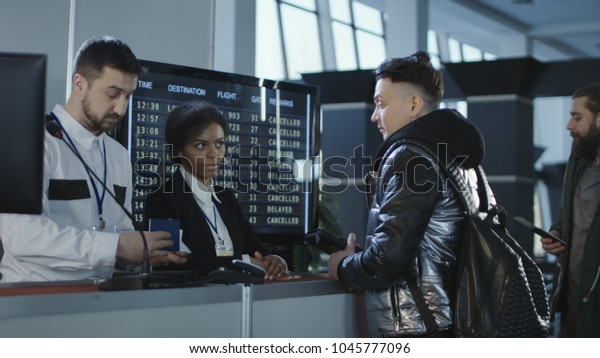 Men and women walking through counter with multiethnic employees in airport passing biometric and passport control.