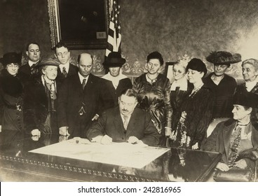 Men and women witness as Colorado governor, Oliver H. Shoup, signs a ratification document for the 19th amendment granting woman's suffrage. Dec. 12, 1919.