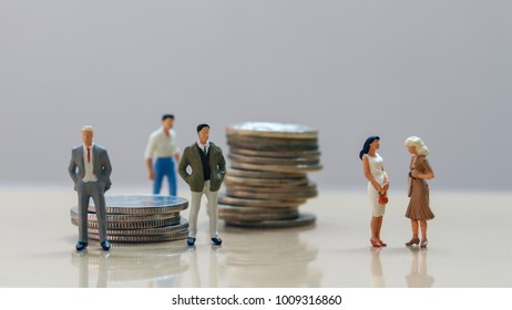 Men and women at work. Men standing in a pile of coins and women standing on the other side.
