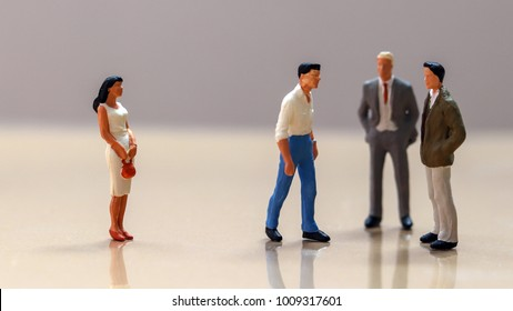 Men and women at work. Miniature woman and a group of miniature men.