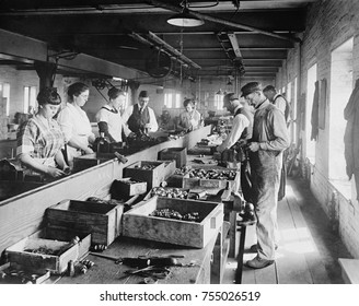 Men and Women working on an assembly line in the Express Spark Plug Co. Ca. 1920, in the Washington, D.C. area.