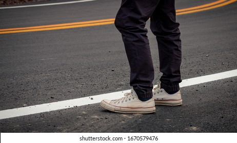 Men wore sneakers standing on paved roads with yellow and white traffic lines crossing the mountains. - Shutterstock ID 1670579476