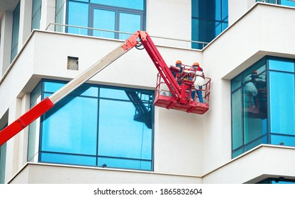 Men at work in hardhat paint facade of the building at height in lifting cradle. Finishing facade work. Construction workers at height working on crane in lifting bucket.