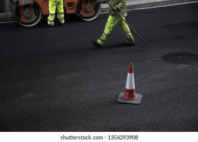 Men at work. Public work. Street paving repair work.
