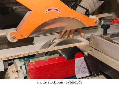 Men at work sawing wood. Circular saw. A machine which saws wood, particle Board and fiberboard. Industrial production of furniture.