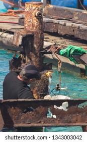 Men at work: worker deconstructing an old and broken steel pier standing in the open sea