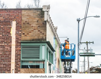a men work,Builder on a Scissor hydraulic  Lift table Platform at a construction site near by the road.