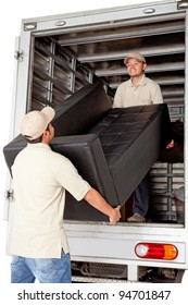 Men working for a moving services company unloading a sofa from a truck