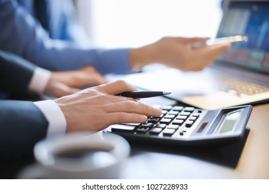 Men working at table in office, closeup. Financial trading concept