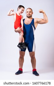 Men in wrestling tights  holds the boy with one hand and they both show bicepson a white isolated background. Dad and son have been fooling around forever.Teaching children Greco-Roman wrestling