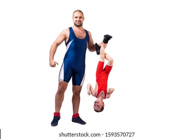 Men in wrestling tights and wrestlers holds the foot of a wrestler boy on a white isolated background. Dad and son have been fooling around forever.Teaching children Greco-Roman wrestling