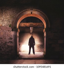 A menacing hooded figure framed in an ancient archway