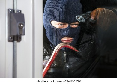 Menacing looking intruder, wearing a balaclava and holding a crow bar and hand gun, looking through the window of a house, ready to break in