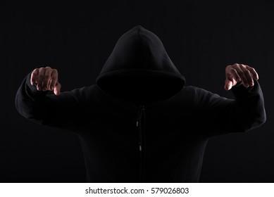 Menacing silhouette of hooded man in the shadow