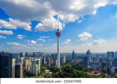 Menara Kuala Lumpur Tower with clouds sky. Aerial view of Kuala Lumpur Downtown, Malaysia. Financial district and business centers in urban city in Asia. Skyscraper and high-rise buildings at noon.