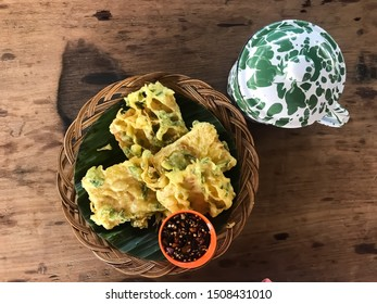 Mendoan or Deep fried tempeh in spiced flour and chopped of leeks, set in bamboo plate, banana leaf underneath. Photographed on wooden table. Very famous traditional snack in Java island.