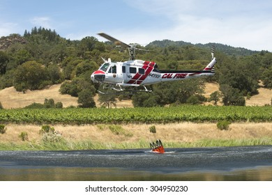 Mendocino County, California, June 20, 2015 - Fire fighting helicopter, run by CalFire, fills its water bucket to fight local brush fire.