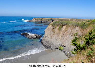 Mendocino Headlands State Park in Mendocino California on a bright, blue, sunny day. Ocean view with rock cliffs, shoreline, and beach