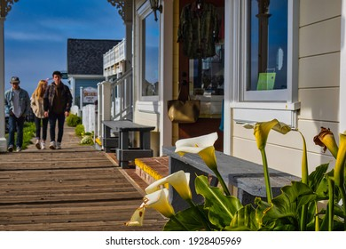 Mendocino, United States - February 16 2020: people walk on wood along the stores in the small and famous town of Mendocino