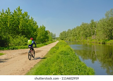 MENDONK, BELGIUM, MAY 4, 2018, Cylist on a pathlush green borders of the canal `de Moer` on a sunny spring day. Mendonk, 4 May 2018