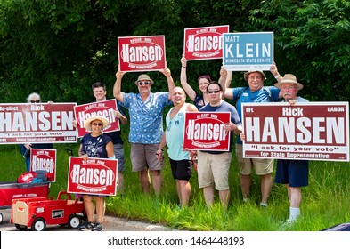 MENDOTA, MN/USA –JULY 13, 2019: Members of local unit of Minnesota Democratic Farmer Labor party hold up signs supporting representatives at Mendota Days Parade.
