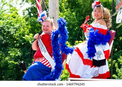 MENDOTA, MN/USA –JULY 13, 2019: Royal Order of Klondike Kates waves to crowd from atop float at annual Mendota Days Parade.