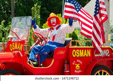 MENDOTA, MN/USA –JULY 13, 2019: St. Paul Osman Shrine Circus Clown gestures to crowd from motorcade at annual Mendota Days Parade.
