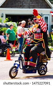 MENDOTA, MN/USA –JULY 13, 2019: St. Paul Osman Shrine Clown on bicycle waves to crowd from motorcade at annual Mendota Days Parade.