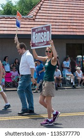 MENDOTA, MN/USA – JULY 14, 2018: Supporters of candidates Rick Hansen and Angie Craig march in annual Mendota Days Parade holding campaign signs.