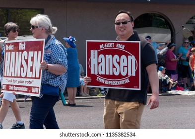 MENDOTA, MN/USA – JULY 14, 2018: Supporters of Minnesota State Representative Rick Hansen march in annual Mendota Days Parade holding campaign signs.