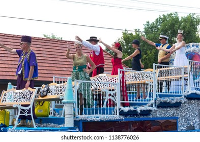 MENDOTA, MN/USA – JULY 14, 2018: St. Paul Winter Carnival Royalty atop float waves to crowd at annual Mendota Days Parade.
