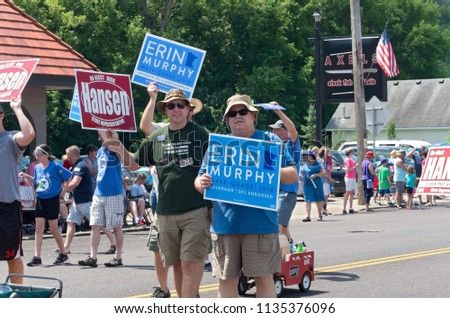 MENDOTA, MN/USA – JULY 14, 2018: Supporters of candidates Erin Murphy and Rick Hansen march in annual Mendota Days Parade holding campaign signs.