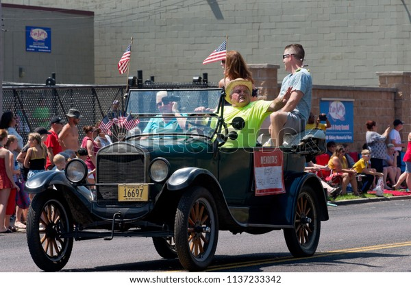 MENDOTA, MN/USA – JULY 14, 2018: Mayor of Mendota in motorcade smiling at spectators during annual Mendota Days Parade.