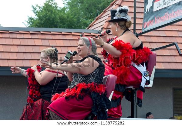 MENDOTA, MN/USA – JULY 14, 2018: St. Paul Winter Carnival Royal Order of Klondike Kates from atop float sings to crowd at annual Mendota Days Parade.