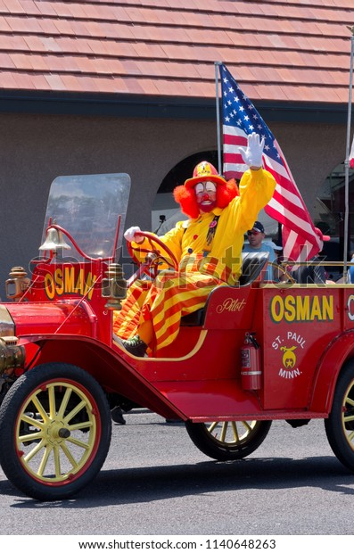MENDOTA, MN/USA – JULY 14, 2018: Osman Shriners circus clown waves to crowd from decorated vehicle at annual Mendota Days Parade.