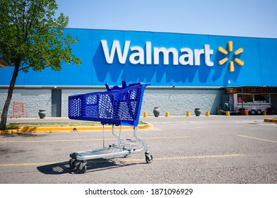 Mendoza, Argentina - January, 2020: Shopping cart on a parking lot in front of main entrance to Walmart supermarket outdoor on the street with no people. Big Walmart logo on blue background behind.