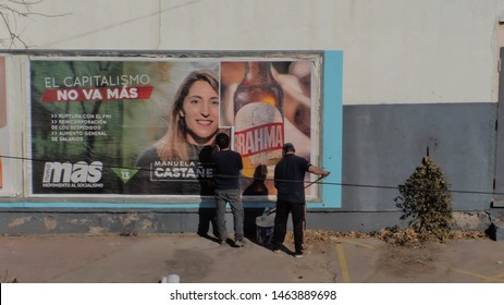 Mendoza, Argentina; July 27th 2019; Bill sticker working; Two men putting street advertising and political propaganda; Election year in Argentina; Political party's propaganda