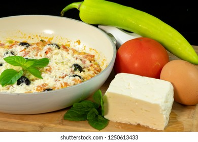 Menemen with tomatoes, egg, green pepper, olives, halloumi cheese, basil, thyme and mint